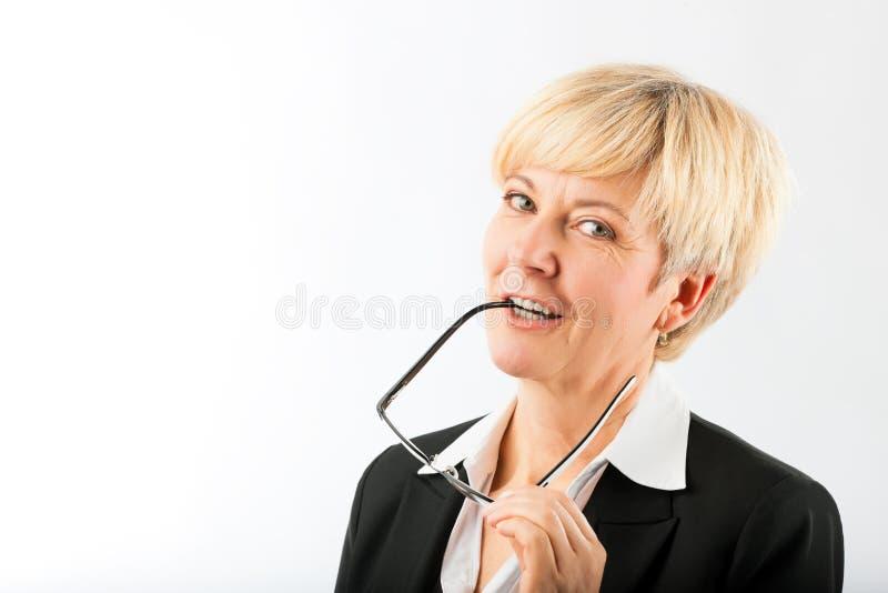 Femme d'affaires mûre avec l'écouteur de lunettes dans la bouche photographie stock libre de droits