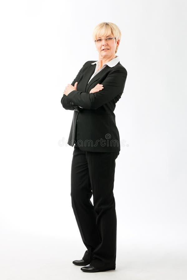Femme d'affaires mûre avec ses bras pliés photographie stock