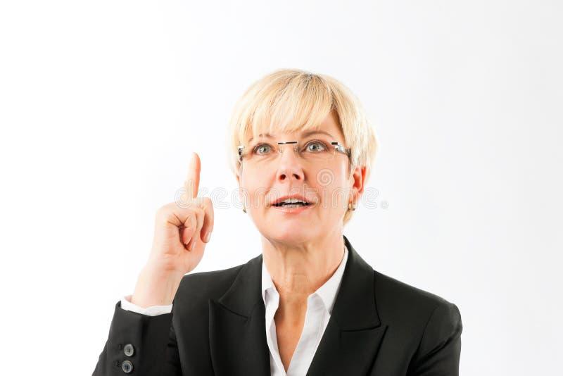 Femme d'affaires mûre de sourire dirigeant le doigt vers le haut photographie stock libre de droits