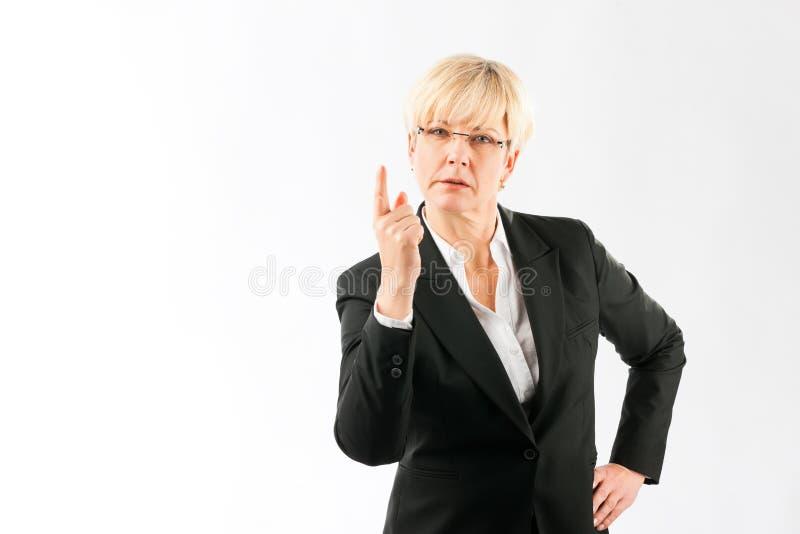 Femme d'affaires mûre dirigeant le doigt vers le haut photo libre de droits