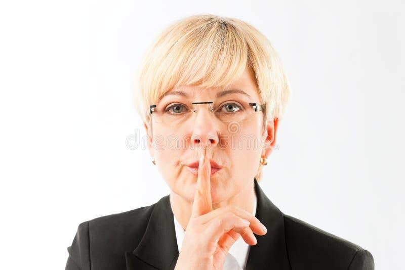 Femme d'affaires mûre faisant le geste silencieux images libres de droits
