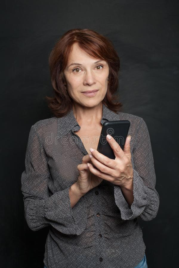 Femme d'affaires mûre heureuse avec le smartphone photographie stock
