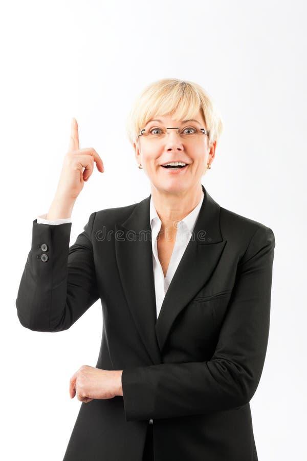 Femme d'affaires mûre heureuse dirigeant le doigt vers le haut photographie stock libre de droits