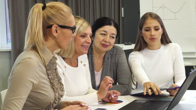 Femme d'affaires mûre montrant quelque chose sur l'ordinateur portable à ses collègues image stock