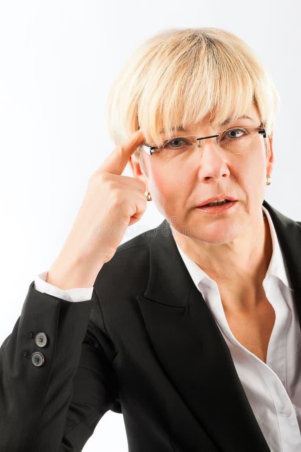Femme d'affaires mûre réfléchie avec des lunettes image libre de droits