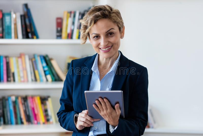 Femme d'affaires mûre riante travaillant au comprimé image libre de droits
