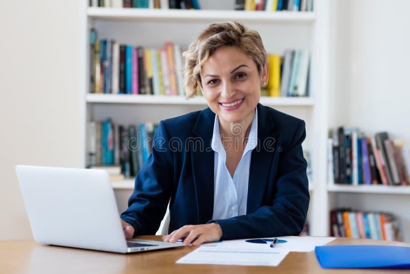 Femme d'affaires mûre riante travaillant sur l'ordinateur photos stock