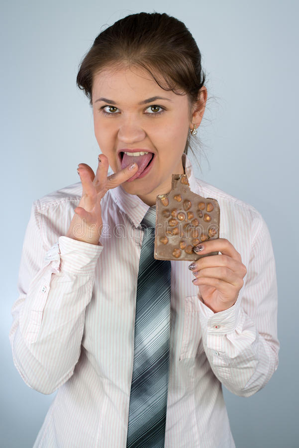 Femme d'affaires mangeant du chocolat photos stock