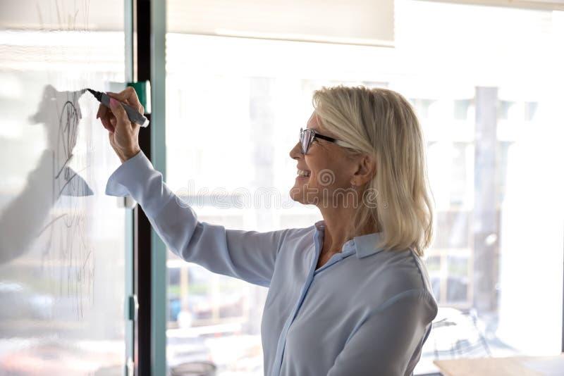 Femme d'affaires mature souriante dessinant des graphiques sur un tableau à feuilles mobiles photographie stock