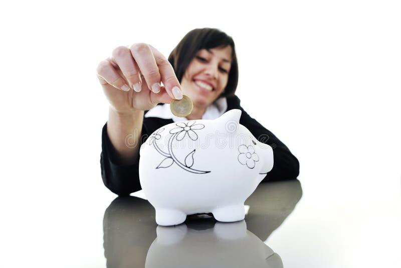 Femme d'affaires mettant l'argent de pièces de monnaie à la tirelire images libres de droits