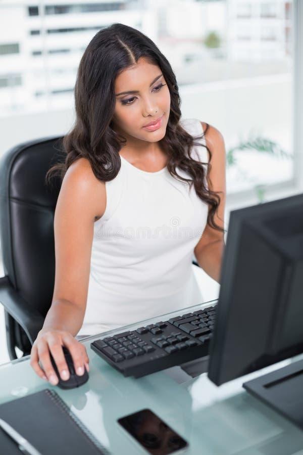 Femme d'affaires mignonne calme s'asseyant derrière le bureau à l'ordinateur photo libre de droits
