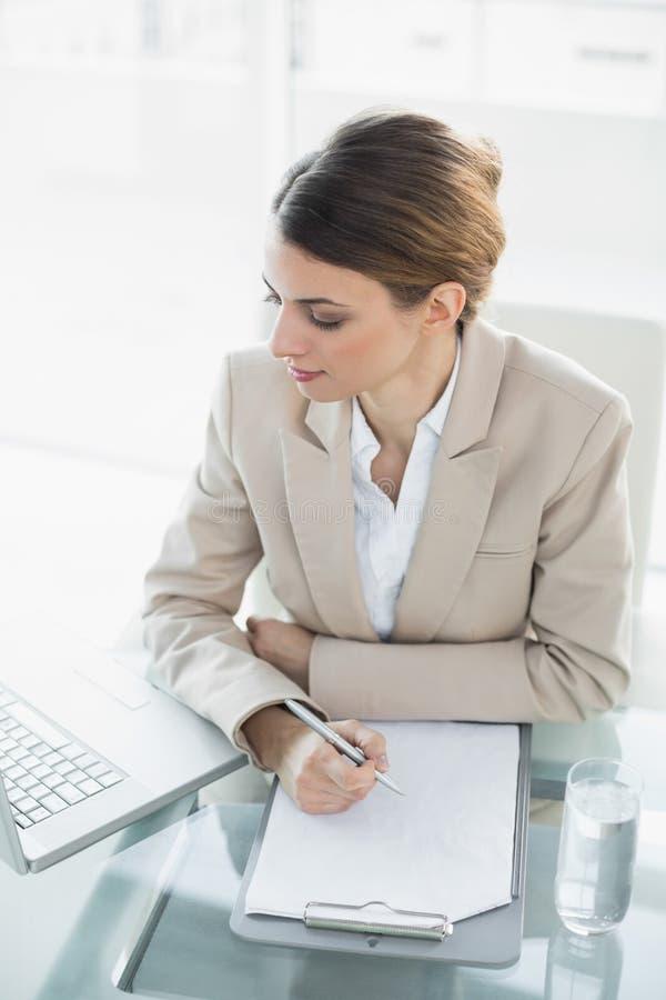 Femme d'affaires mignonne de brune travaillant avec un presse-papiers et un carnet photo libre de droits