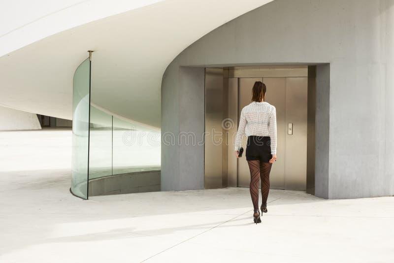 Femme d'affaires moderne à la mode entrant dans le bâtiment d'entreprise images stock
