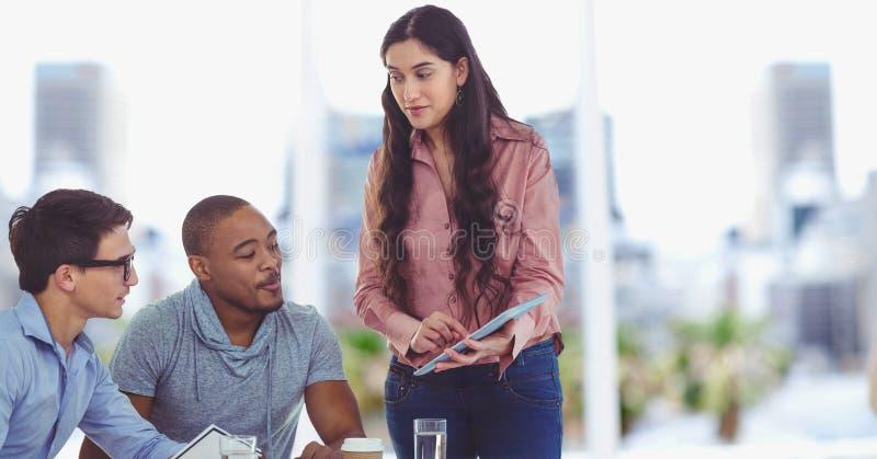 Femme d'affaires montrant des données sur le comprimé numérique aux collègues images stock