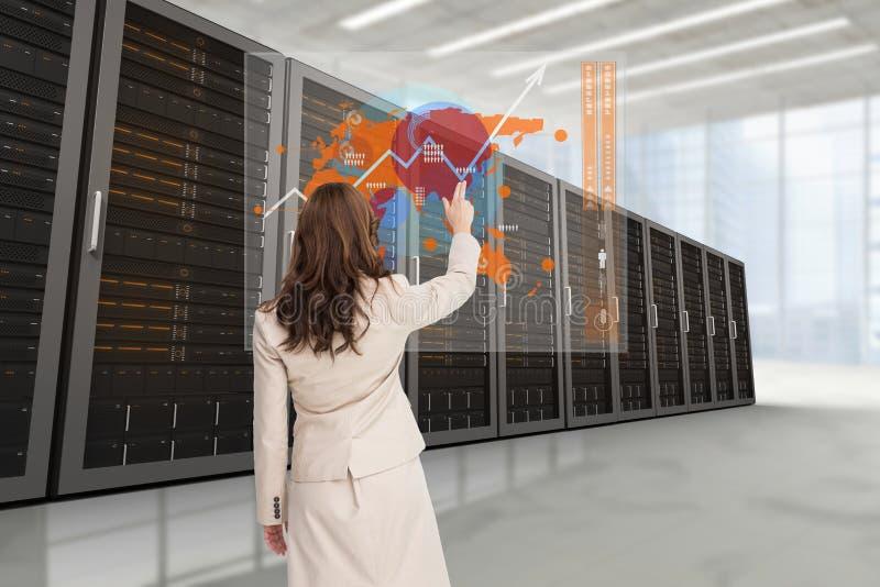 Femme d'affaires montrant les graphiques du dos sur le fond de centre de traitement des données illustration libre de droits