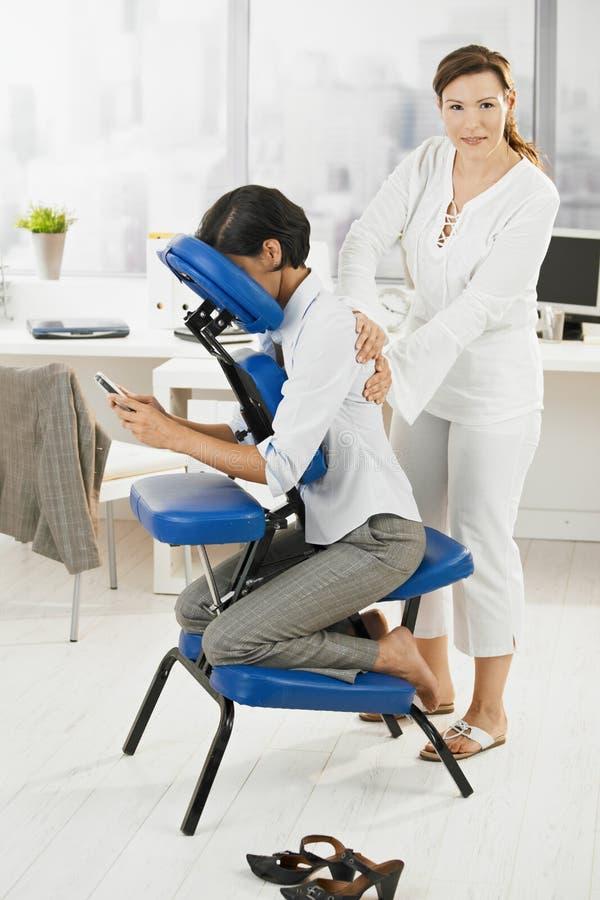 Femme d'affaires obtenant le massage dans le bureau image libre de droits