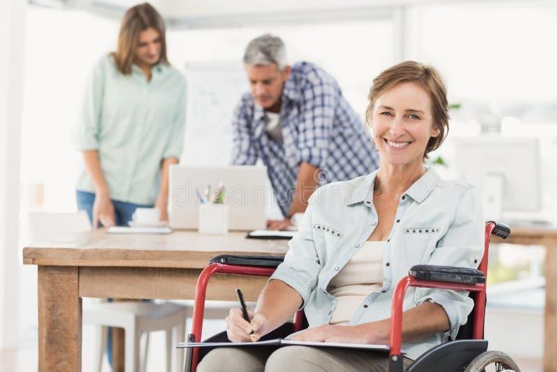 Femme d'affaires occasionnelle dans le fauteuil roulant avec le bloc-notes photos libres de droits