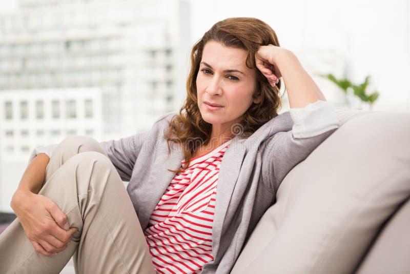 Femme d'affaires occasionnelle inquiétée s'asseyant sur le divan photo libre de droits