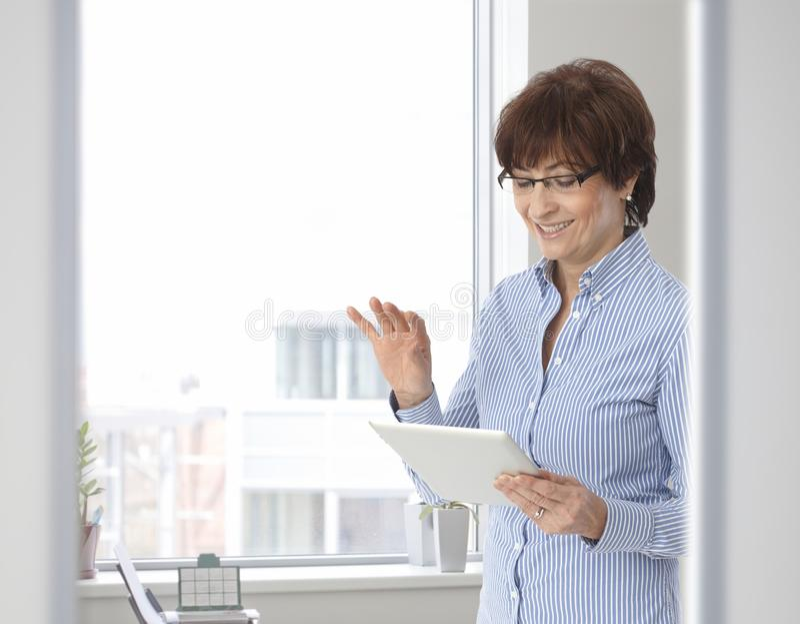 Femme d'affaires occasionnelle supérieure avec la tablette photographie stock libre de droits