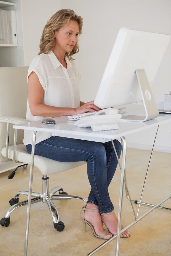 Femme d'affaires occasionnelle travaillant à son bureau images libres de droits