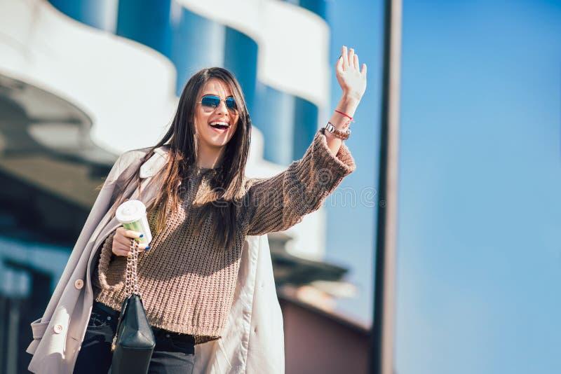 Femme d'affaires occupée attirante appelle le taxi, la pousse extérieure avec les bâtiments brouillés et la rue comme fond photos stock