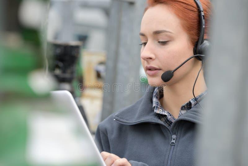 Femme d'affaires occupée au téléphone vérifiant le comprimé photographie stock