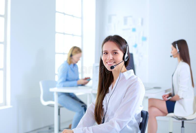 Femme d'affaires ou opérateur de sourire de service d'assistance avec le casque et l'ordinateur au bureau photos libres de droits