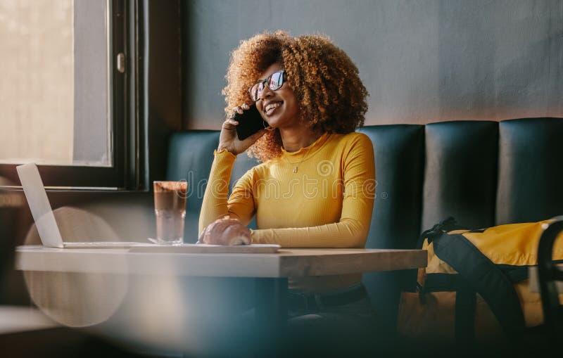 Femme d'affaires parlant au-dessus du téléphone portable se reposant à un restaurant photo libre de droits