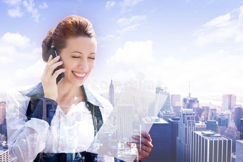 Femme d'affaires parlant au téléphone intelligent regardant des papiers de documents sur le paysage urbain de double exposition photo libre de droits