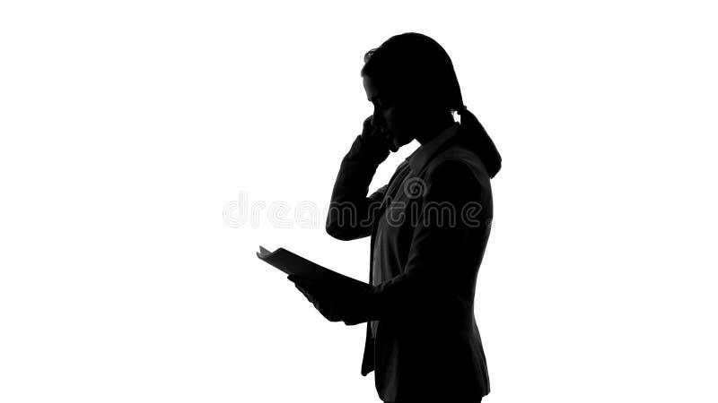 Femme d'affaires parlant au téléphone, organisant la réunion, vérifiant l'ordre du jour, silhouette photographie stock libre de droits