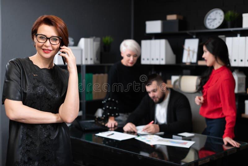 Femme d'affaires parlant au téléphone sur le fond des employés de bureau discutant le projet photographie stock libre de droits