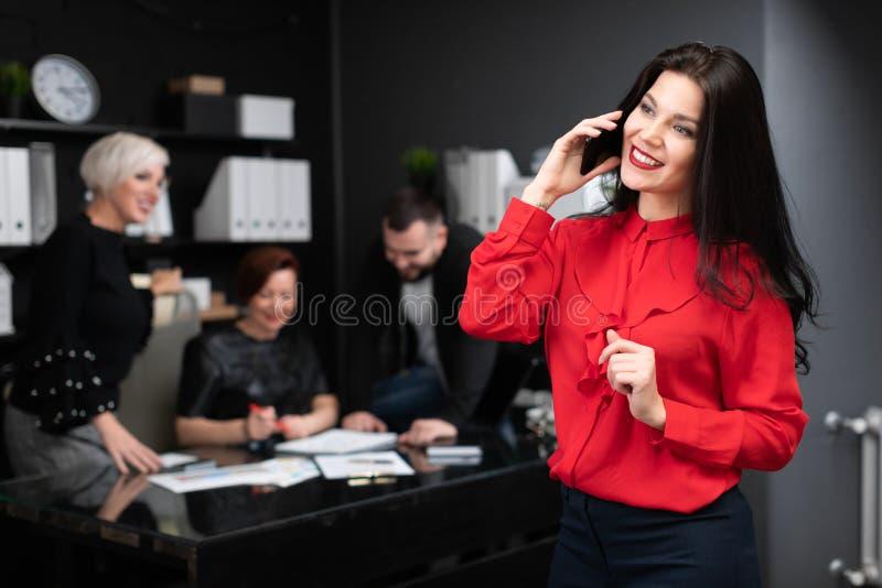Femme d'affaires parlant au téléphone sur le fond des employés de bureau discutant le projet photos libres de droits