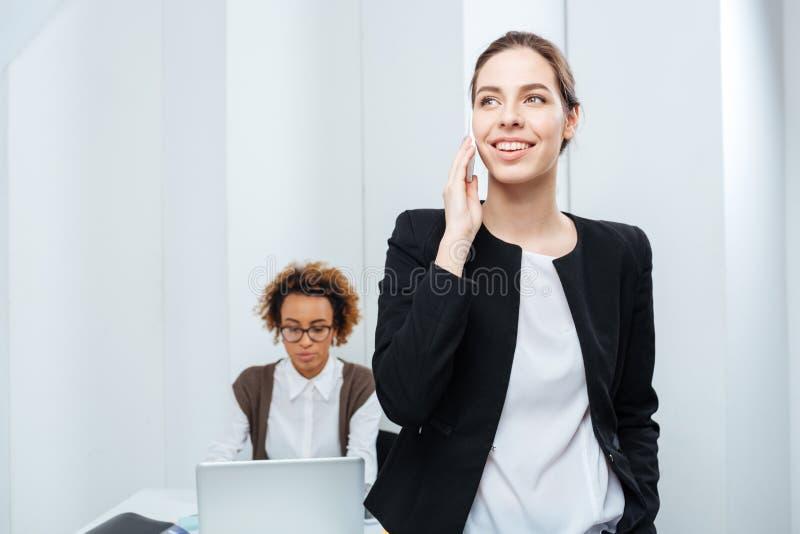 Femme d'affaires parlant au téléphone tandis que son collègue travaillant avec l'ordinateur portable image libre de droits