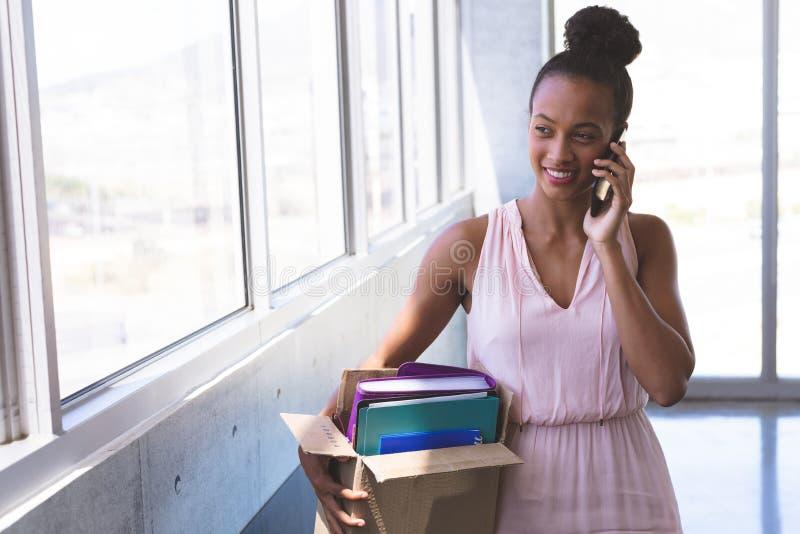 Femme d'affaires parlant au t?l?phone portable tout en tenant des substances dans le bureau images stock