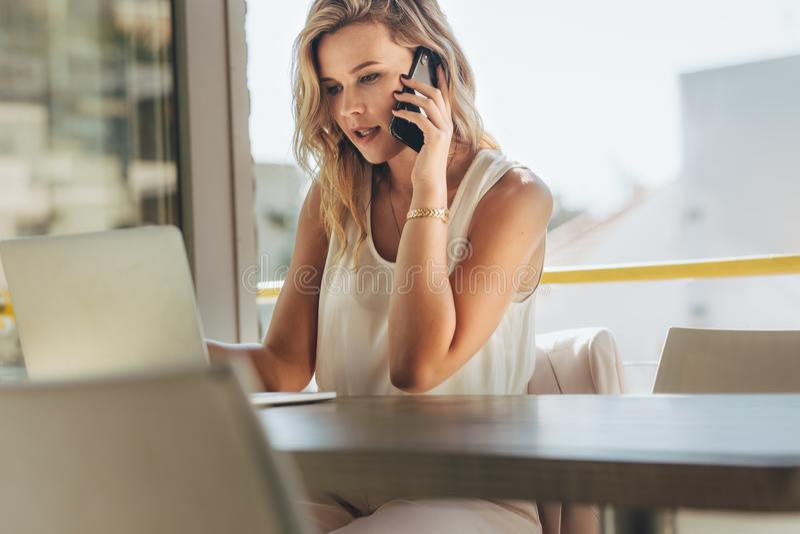 Femme d'affaires parlant avec le client au-dessus du téléphone en café photos libres de droits
