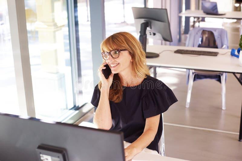 Femme d'affaires parlant avec quelqu'un sur un téléphone portable pendant qu'elle travaille au bureau photos libres de droits