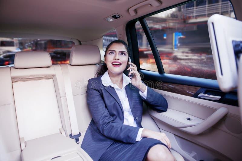 Femme d'affaires parlant sur le téléphone portable à l'intérieur de la voiture photos libres de droits