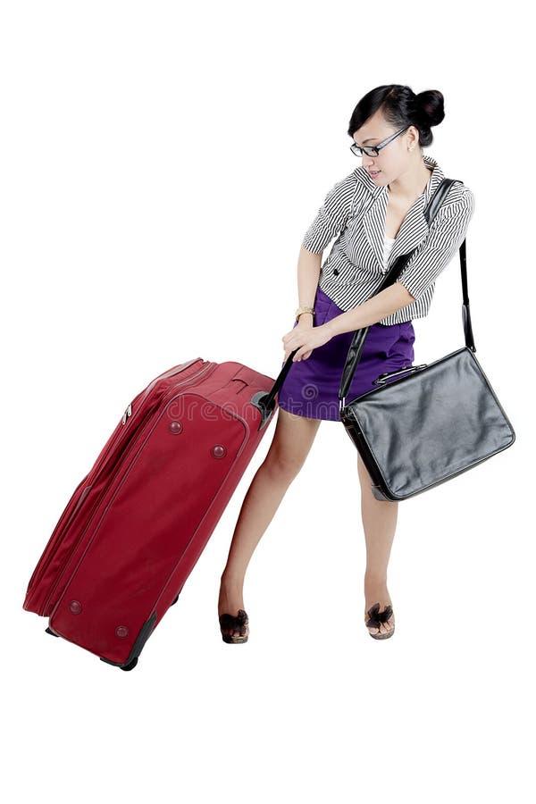 Femme d'affaires portant des bagages lourds sur le studio photographie stock