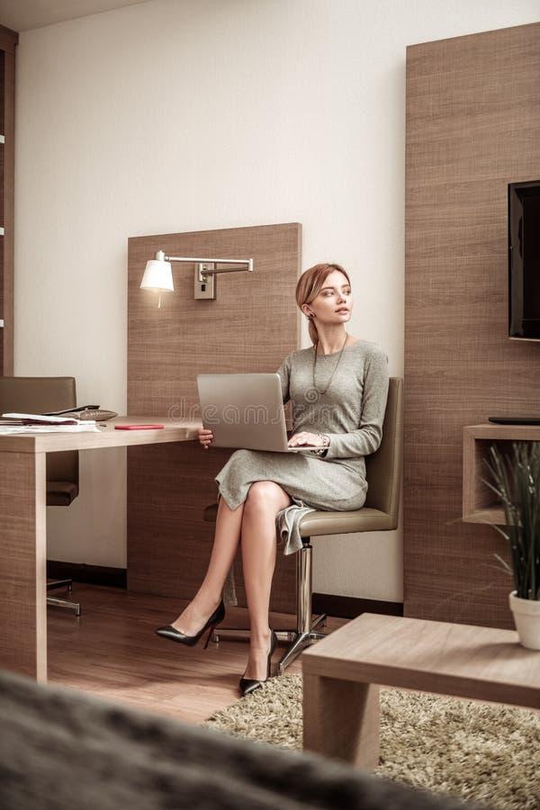 Femme d'affaires portant les vêtements élégants lisant la lettre commerciale sur l'ordinateur portable photos libres de droits
