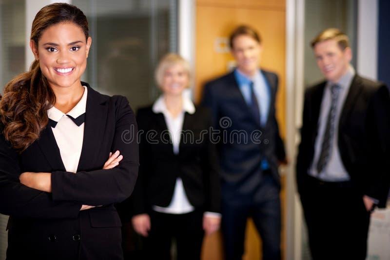 Femme d'affaires posant avec les associés futés derrière photographie stock libre de droits