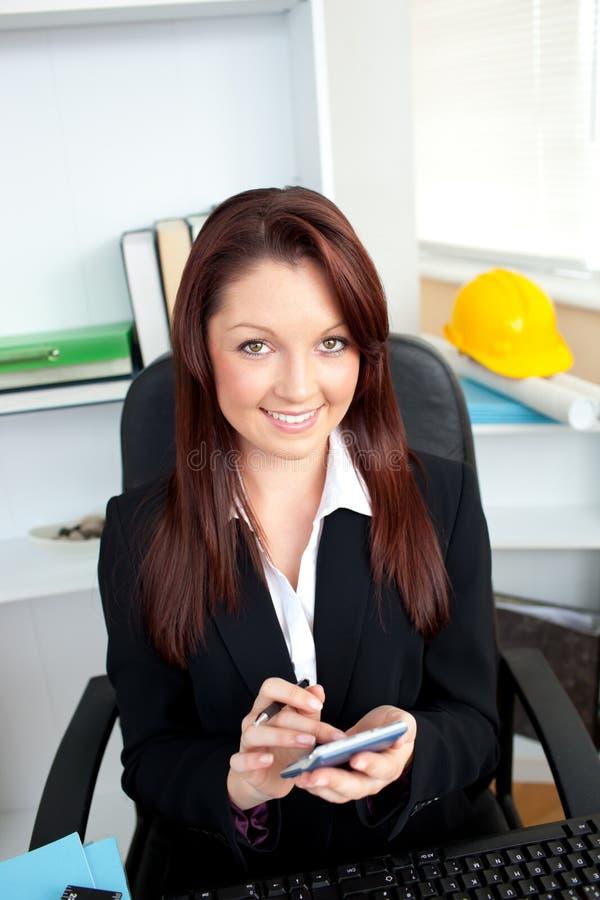 Femme d'affaires positive à l'aide de sa calculatrice photos libres de droits