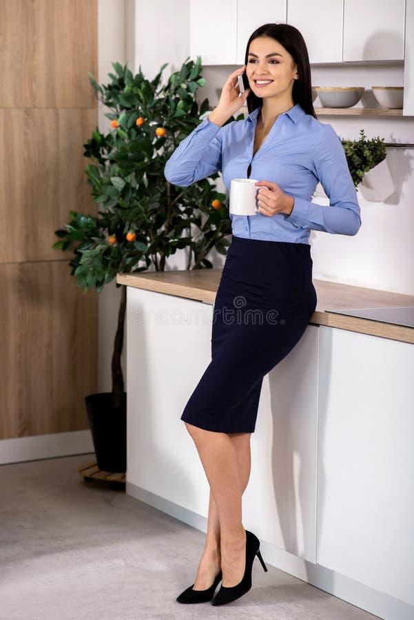 Femme d'affaires positive se tenant dans la cuisine photos libres de droits