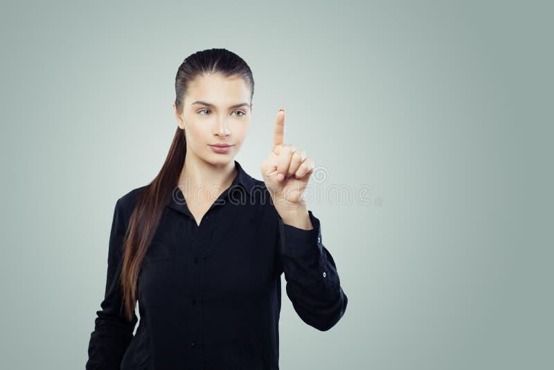 Femme d'affaires poussant l'espace vide de copie sur le fond gris Portrait amical de femme images stock
