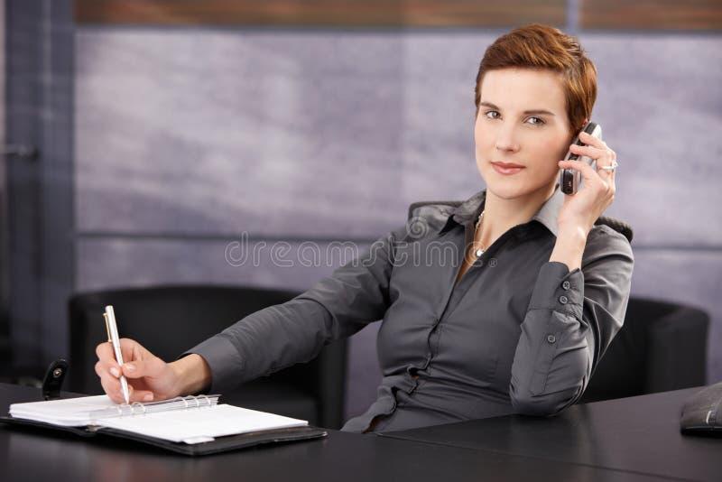 Femme d'affaires prenant des notes tandis qu'à l'appel téléphonique photographie stock
