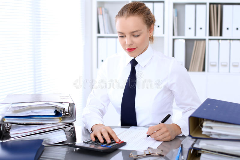 Femme d'affaires rédigeant le rapport, calculant ou vérifiant l'équilibre photographie stock libre de droits