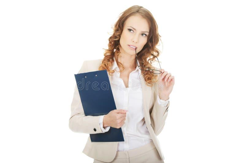 Femme d'affaires réfléchie avec le presse-papiers photographie stock libre de droits