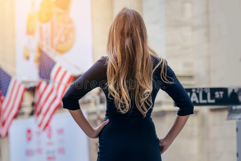 Femme d'affaires réussie et puissante se tenant près de la bourse des valeurs dans la rue de New York City photographie stock