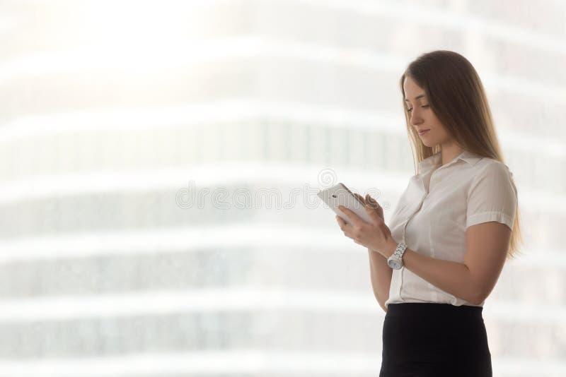 Femme d'affaires réussie sûre se tenant utilisant le comprimé numérique photographie stock libre de droits