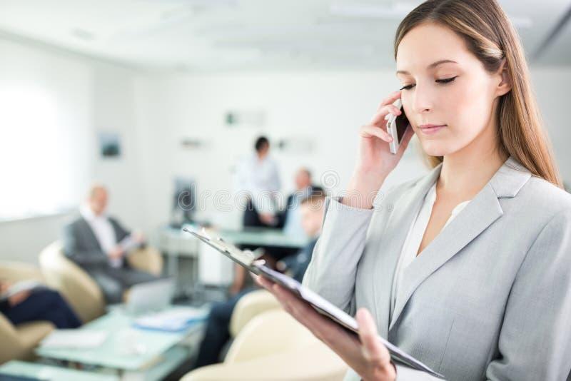 Femme d'affaires Reading Document While employant Smartphone dans le bureau image libre de droits