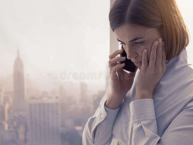 Femme d'affaires recevant un appel téléphonique dans le bureau image stock
